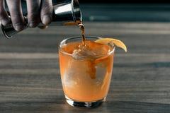 Empregado de bar do barman com o cocktail que prepara o cocktail alaranjado na barra Bebidas do álcool imagens de stock