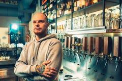 Empregado de bar em um bar perto das torneiras da cerveja fotos de stock royalty free