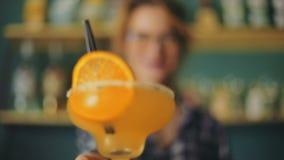 Empregado de bar fêmea do barista do barman que apresenta a palha frutado da fatia da parte martini de vidro cocktail alaranjado  vídeos de arquivo