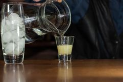 Empregado de bar na soda de derramamento do contador do jarro no vidro com suco fotos de stock
