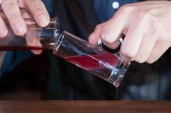 Empregado de bar no cocktail de fatura contrário do álcool na barra fotos de stock