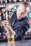 Empregado de bar profissional que faz a bebida alcoólica do cocktail antiquado fotografia de stock