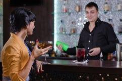 Empregado de bar que conversa com um cliente fêmea imagem de stock royalty free