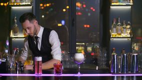 Empregado de bar que decora o cocktail com palhas filme