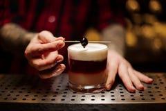 Empregado de bar que decora o cocktail doce alcoólico flocoso com uma cereja imagens de stock