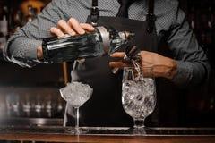 Empregado de bar que derrama a bebida alcoólica em um vidro usando um jigger para preparar um cocktail imagens de stock