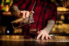 Empregado de bar que derrama o cocktail alcoólico forte fresco em um vidro na barra foto de stock