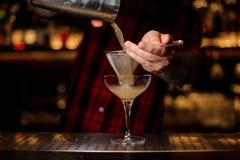 Empregado de bar que derrama o cocktail alcoólico suculento do abanador no vidro de cocktail fotografia de stock royalty free