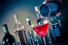 Empregado de bar que derrama um cocktail vermelho em um vidro com gelo Imagens de Stock Royalty Free