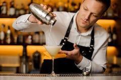 Empregado de bar que derrama uma bebida alcoólica fresca em um vidro de cocktail Fotos de Stock