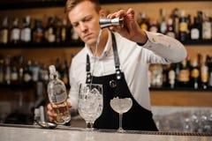 Empregado de bar que derrama uma parcela de vodca em um vidro Fotografia de Stock