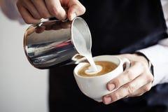 Empregado de bar que faz o café, leite de derramamento Fotografia de Stock Royalty Free