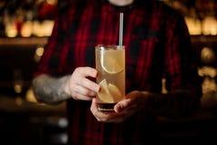 Empregado de bar que guarda um vidro do cocktail alaranjado alcoólico fresco imagem de stock