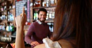 Empregado de bar que interage com o traje fêmea no contador da barra video estoque