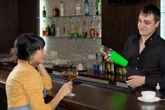 Empregado de bar que mistura um cocktail para um cliente fêmea imagem de stock