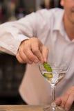 Empregado de bar que põe a casca de limão para preparar o coctail imagens de stock royalty free