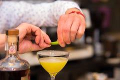 Empregado de bar que põe a casca de limão para preparar o coctail foto de stock