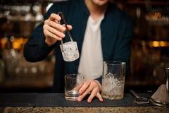 Empregado de bar que põe uma parte grande de cubo de gelo em um vidro Foto de Stock