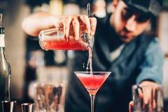 Empregado de bar que prepara e que derrama o cocktail vermelho na classe de martini cocktail cosmopolita com fundo da barra Fotografia de Stock Royalty Free