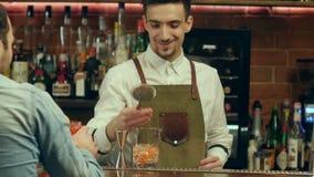 Empregado de bar que prepara o cocktail para um cliente e que espera sua reação filme