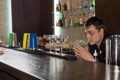 Empregado de bar que verifica os vidros alinhados na barra imagem de stock royalty free