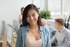 Empregado de escritório asiático de sorriso que olha a câmera que trabalha com colo imagens de stock royalty free