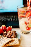 Empregado de escritório com portátil, o petisco saudável, a água com morango e o pepino Foto de Stock