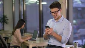 Empregado de escritório que conversa no mensageiro social dos meios no smartphone, uma comunicação vídeos de arquivo