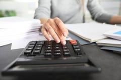 Empregado de escritório que trabalha com calculadora e documentos na tabela foto de stock