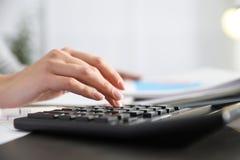 Empregado de escritório que trabalha com calculadora e documentos na tabela fotografia de stock