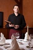 Empregado de mesa masculino com o menu do dobrador nas mãos Imagens de Stock Royalty Free
