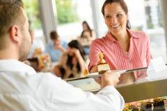 Empregado de mesa que dá a placa do bolo da mulher no café imagem de stock
