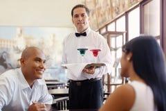 Empregado de mesa que está com a bandeja no restaurante Fotos de Stock Royalty Free