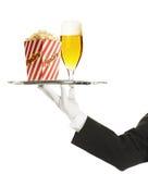 Empregado de mesa que prende uma bandeja com um vidro de cerveja e um popcor fotos de stock royalty free