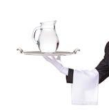 Empregado de mesa que prende uma bandeja de prata com um jarro Foto de Stock Royalty Free