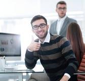 Empregado de sorriso que senta-se atrás de uma mesa imagens de stock royalty free
