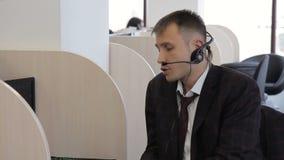 Empregado do centro de atendimento que fala ao sentar-se no escritório moderno filme