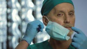 Empregado do hospital no dever que descola a máscara protetora, tomando da saúde dos pacientes vídeos de arquivo