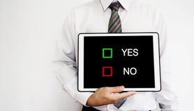 Empregado do negócio que guarda a tabuleta digital com YES ou NENHUMA seleção das escolhas na tela Imagem de Stock