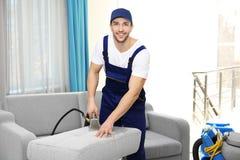 Empregado do ` s do líquido de limpeza seco que remove a sujeira da mobília foto de stock royalty free