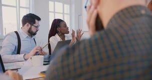 Empregado do sexo feminino afro-americano novo feliz que discute o projeto com o líder da equipe da mulher de negócios na reuni filme