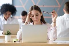 Empregado do sexo feminino cansado que sofre da dor de cabeça no local de trabalho imagens de stock royalty free
