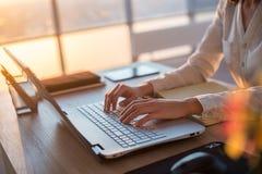 Empregado do sexo feminino concentrado que datilografa no local de trabalho usando o computador Retrato da vista lateral de um re fotos de stock royalty free