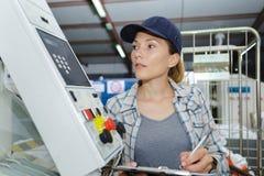 Empregado do sexo feminino da fabricação que guarda a prancheta e a anotação foto de stock royalty free