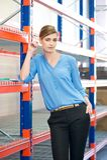 Empregado do sexo feminino do armazém que está ao lado das prateleiras Fotos de Stock