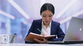 Empregado do sexo feminino novo que escreve no caderno, dia planejando do trabalho, ideias, disciplina filme