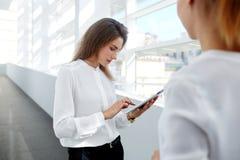 Empregado do sexo feminino profissional que trabalha na tabuleta digital quando seu sócio que está próximo no interior moderno do Imagem de Stock