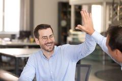 Empregado do sexo masculino feliz que dá altamente cinco ao colega fotografia de stock royalty free