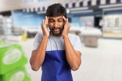 Empregado do supermercado com enxaqueca fotos de stock royalty free