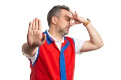 Empregado do supermercado que faz o gesto bruto do cheiro imagem de stock royalty free